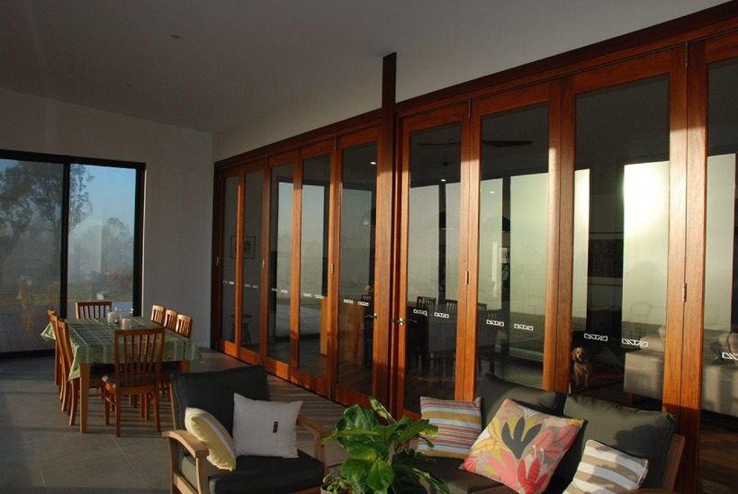 Teal wooden bifold doors in high traffic area of hotel external view