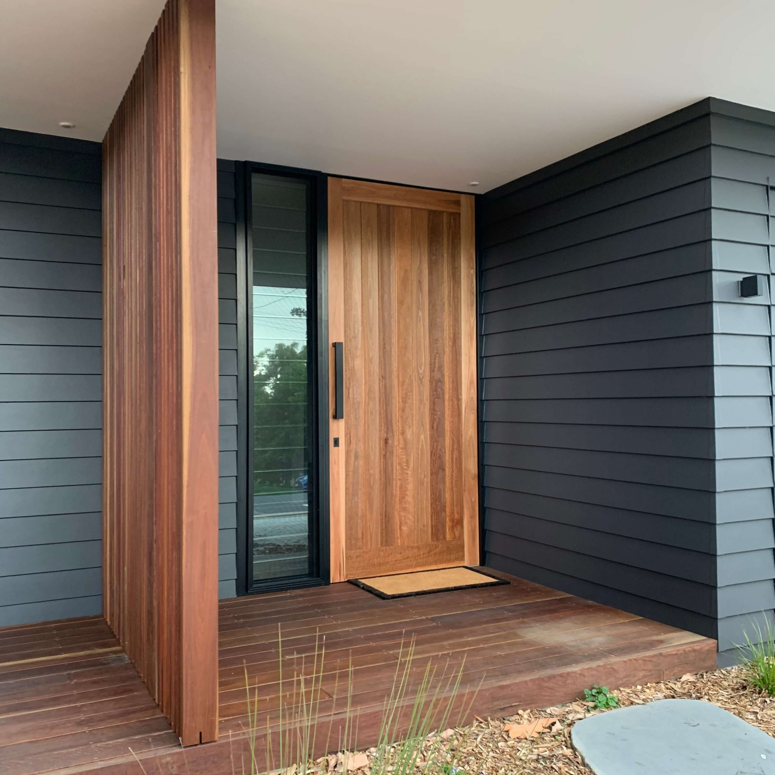 Timber shiplap front door with black hardware accompanied by a full length glass louvre window