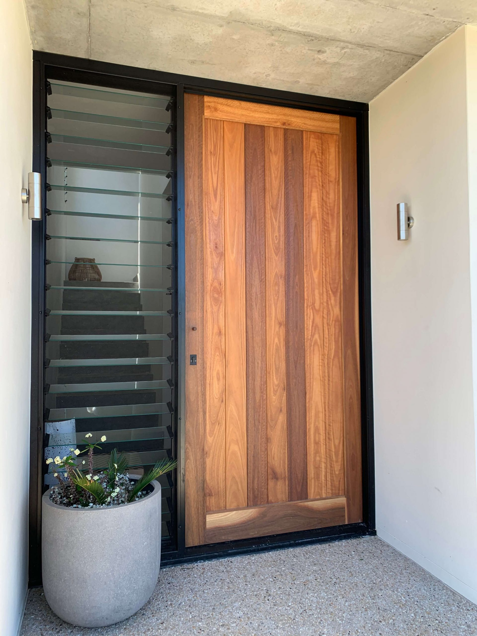Architectural home with a large Spotted Gum vertical VJ pivot entry door unit with a clear glass sidelight