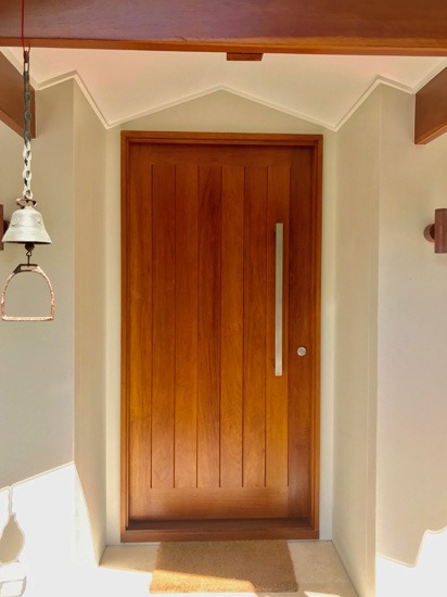Simple flush vertical panelled solid timber house entrance door with a long satin chrome handle and lock