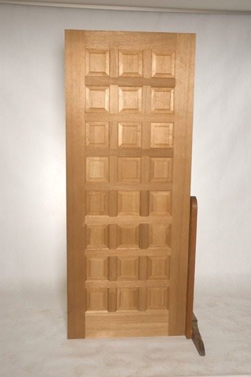 Single wooden entrance door with twenty-four raised timber panels eight high three wide